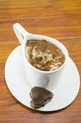 Cup of coffee and a heart shaped chocolate