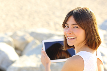 Woman using a tablet and looking at camera