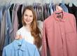 Leinwanddruck Bild - Mitarbeiterin in Wäscherei präsentiert zwei Hemden den Händen
