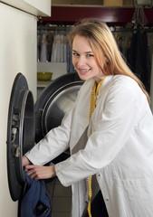 Mitarbeiterin in Wäscherei belädt eine Trockenreinigungsmaschine