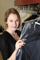 Frau in Textilreinigung mit Wäsche in Folie verpackt