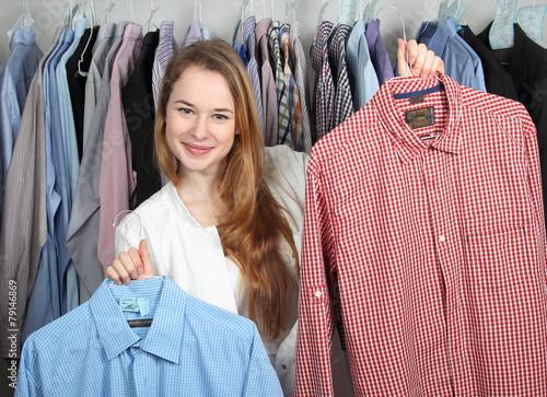 Leinwanddruck Bild Mitarbeiterin in Wäscherei präsentiert zwei Hemden den Händen