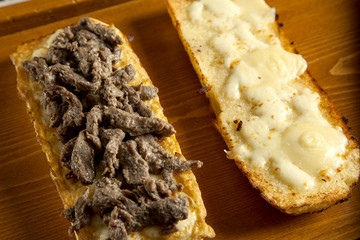 toasted open faced beef steak sandwich with melted mozzarella ch