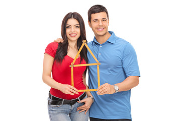 Couple holding a tape measure in form of house