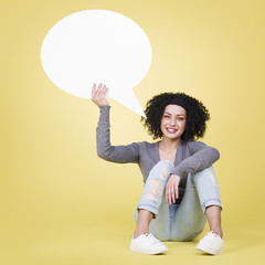 Happy girl holding a blank speech balloon with copy space.