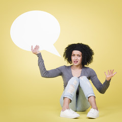 Annoyed girl holding white speech balloon with copyspace.