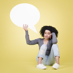 Unhappy girl holding a white speech balloon with copyspace.