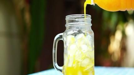 Pouring orange juice into a glass jar