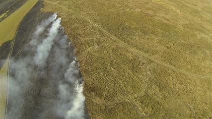 Flight over fire smoke in  steppe. Aerial shot  top view