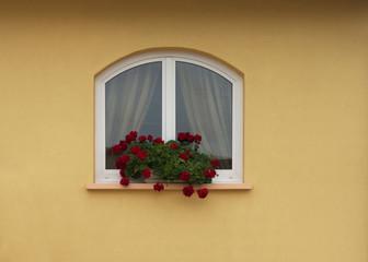 Modernes Rundbogenfenster aus PVC mit Blumenschmuck
