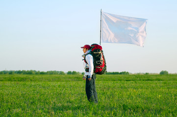 Hiker with backpack and flag standing in the field