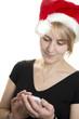 Mädchen mit Nikolausmütze schreibt eine SMS