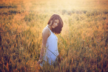 Beautiful young woman in a summer field