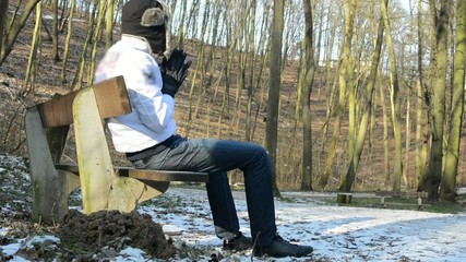 man sitting in winter park - sunny - bare forest