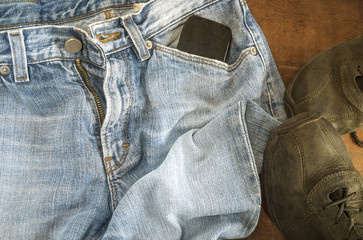 Detail of blue jeans with black shoes on wooden background