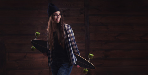 Hipster girl in glasses with a longboard