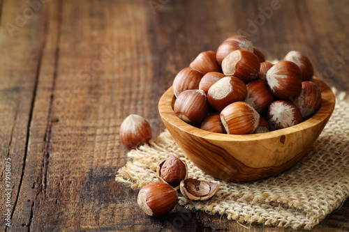 Plexiglas Aromatische Hazelnuts in a wooden bowl on rustic background