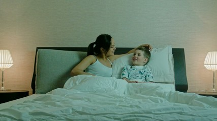 Young mother and her son in a bed