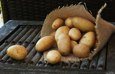 fruits of potatoes on a wooden surface
