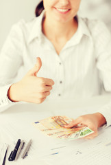 woman hands with euro cash money and thumbs up