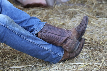 Cowboy with leather boots and jeans in the stable of the ranch