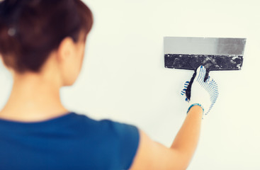 woman plastering the wall with trowel
