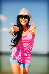 girl showing thumbs up on the beach