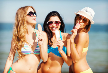 girls in bikini with ice cream on the beach
