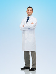 smiling male doctor in white coat over blue