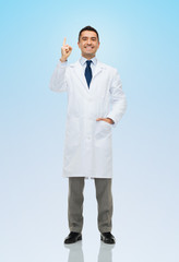 smiling doctor in white coat pointing finger up