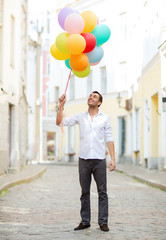 man with colorful balloons in the city