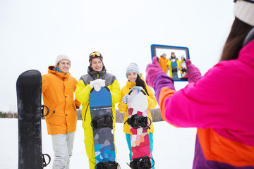 happy friends with snowboards and tablet pc