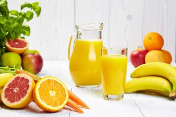 Full glass and jug of banana juice and bananas