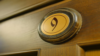 wooden number nine on the door close up