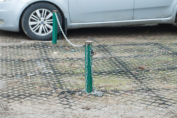 pole iron chain link fence on a street car parking City