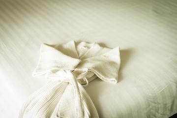 white bathrobe on bed