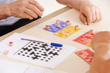 Alte Hände von Senioren beim Bingo spielen