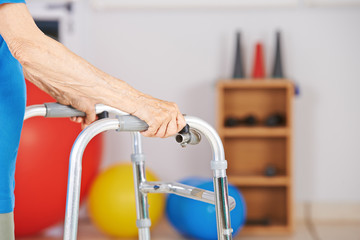 Alte Hände einer Seniorin mit Gehgestell