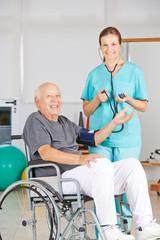 Krankenschwester misst Blutdruck bei Mann im Rollstuhl
