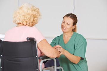 Krankenwester bei der Pflege von Frau im Rollstuhl