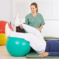 Physiotherapeut bewegt Bein bei Krankengymnastik