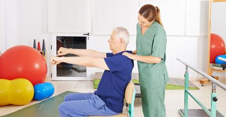 Senior beim Rehasport macht Rückenübung
