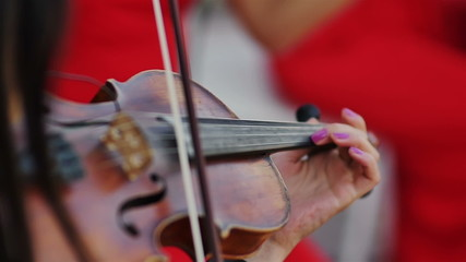 women in red dress musician playing violin extra close up shot