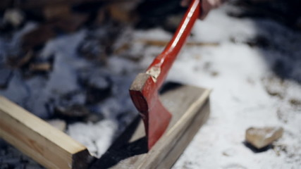Forester chopping wood with an axe close up slow motion