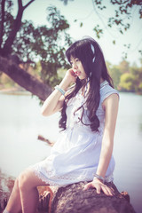 A cute Asian Thai girl is sitting on a tree trunk on the riversi