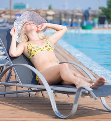 Young woman in swimsuit laying on chaise-longue poolside