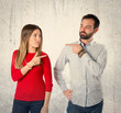 Couple pointing each other over white background