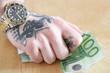 tätowierte Hand mit Luxusuhr hält Geldschein