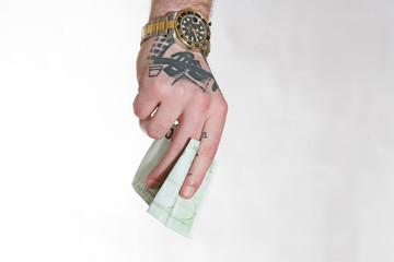 tätowierte Hand mit Luxusuhr hält 100-Euro-Schein
