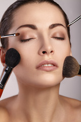 Beauty Girl with Makeup Brushes. Beautiful Face